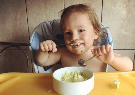 Două mâini, două linguri și o porție de gratin de cartofi cu verdeață